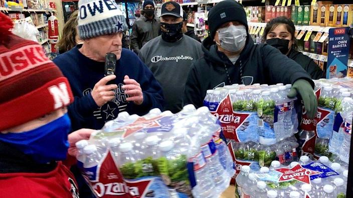 Shoppers crowd a display of bottled water at a supermarket in Abilene, Texas, 15 February 2021
