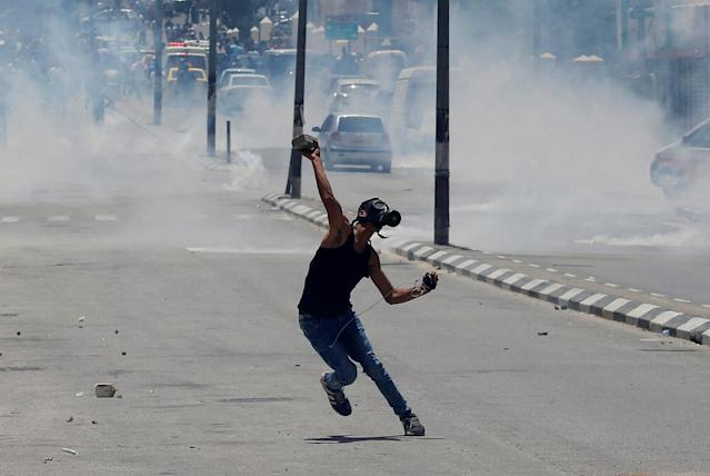 <p>A Palestinian protester hurls stones towards Israeli troops during clashes at a protest marking the 69th anniversary of Nakba, in the West Bank town of Bethlehem May 15, 2017. (Photo: Ammar Awad/Reuters) </p>