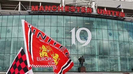 Manchester United supporters wave flags outside the stadium before their English Premier League soccer match against Blackpool at Old Trafford
