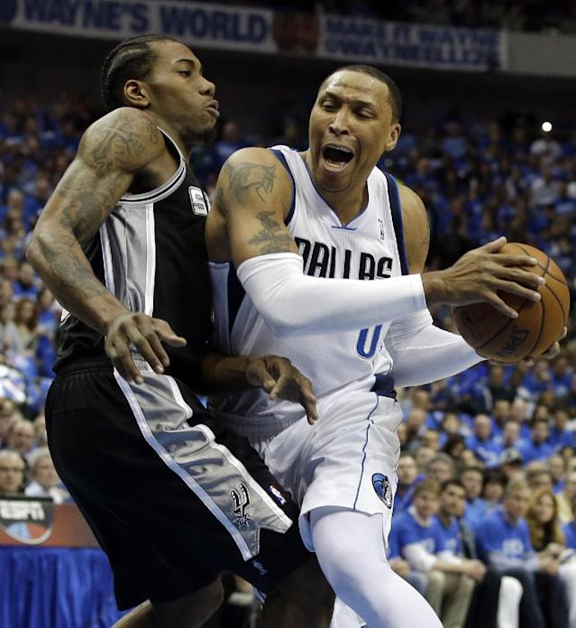 San Antonio Spurs' Kawhi Leonard, left, defends against a drive to the basket by Dallas Mavericks' Shawn Marion, right, in the first half of Game 6 of an NBA basketball first-round playoff series on Friday, May 2, 2014, in Dallas. (AP Photo/Tony Gutierrez)