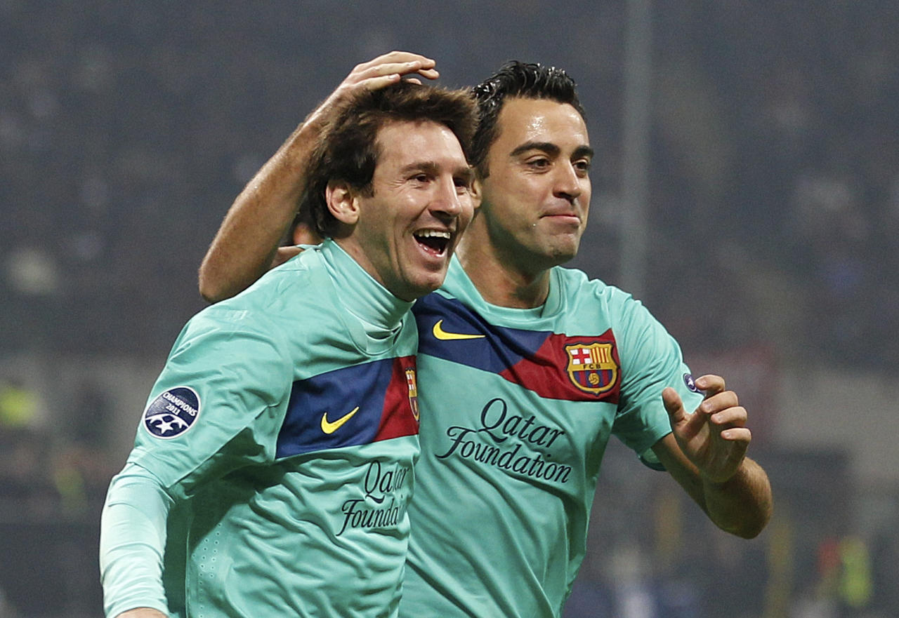 Barcelona forward Lionel Messi, of Argentina, left, celebrates with teammates midfielder Xavi Hernandez after an own goal of AC Milan midfielder Mark Van Bommel, during a Champions League, Group H soccer match between AC Milan and Barcelona at the San Siro stadium in Milan, Italy, Wednesday, Nov.23, 2011. (AP Photo/Luca Bruno)