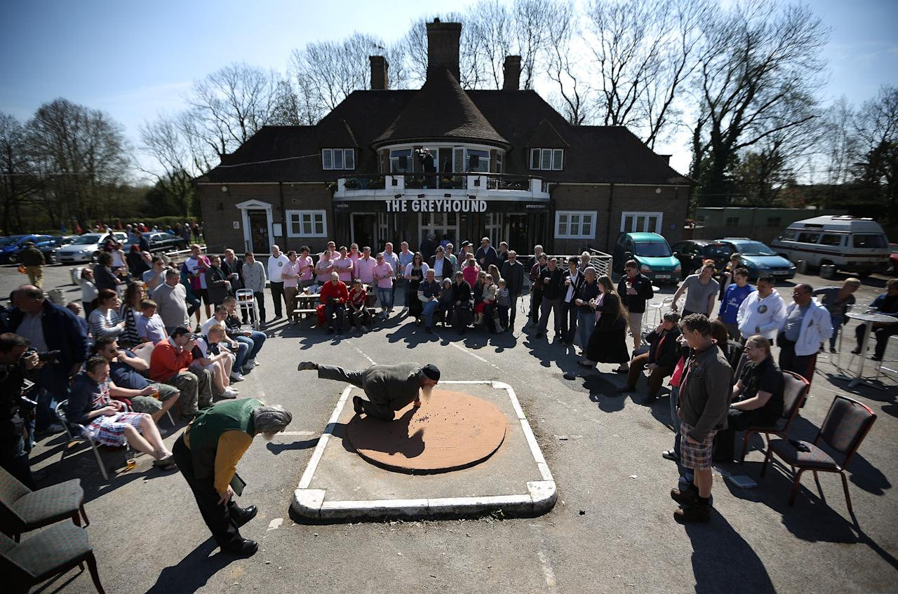 German player Andreas vom Rothenbarth takes a shot in the British and World Marble Championships on April 6, 2012 in Tinsley Green, England.  On Good Friday every year, contestants from all over the world gather at The Greyhound pub in Tinsley Green, Sussex to take part in the Championships. The game is played between two teams of six players in a ring with a diameter of six feet. The object of the game is to knock 25 out of 49 'target marbles' out of the ring using 'tolley' marbles before the opposing team. (Photo by Peter Macdiarmid/Getty Images)