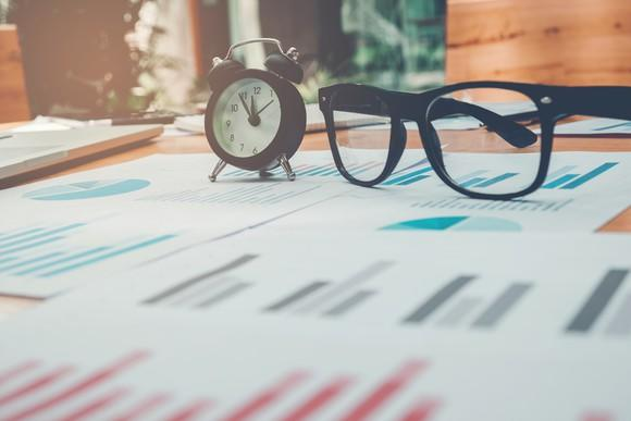 A pair of glasses and an alarm clock sitting on top of papers.