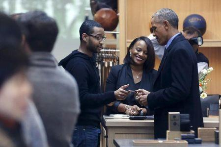 Obama uses a credit card to buy an item at the Shinola watchmakers flagship store in Detroit