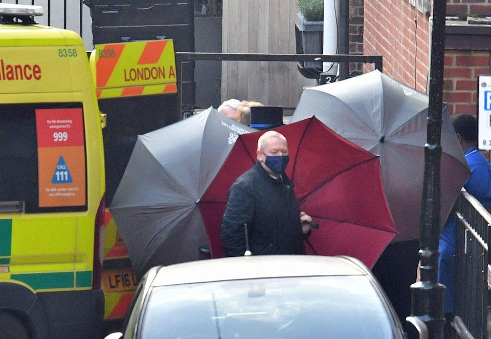 Staff shield the exit with umbrellas alongside an ambulance outside the rear of the hospitalPA