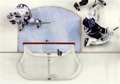 Chicago Blackhawks' Jonathan Toews (19) scores past St. Louis Blues goalie Jaroslav Halak, of Slovakia, during the first period of an NHL hockey game, Thursday, Feb. 28, 2013, in St. Louis. (AP Photo/Jeff Roberson)