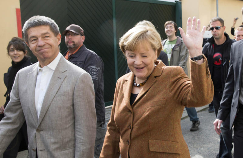 German Chancellor Angela Merkel, chairwoman of the Christian Democratic party CDU, waves to residents next to her husband Joachim Sauer, left, as they walk back after casting their votes in Berlin, Sunday, Sept. 22, 2013. 62 million voters in Germany are entitled to elect a new parliament as Merkel runs for her third term as chancellor. (AP Photo/Gero Breloer)