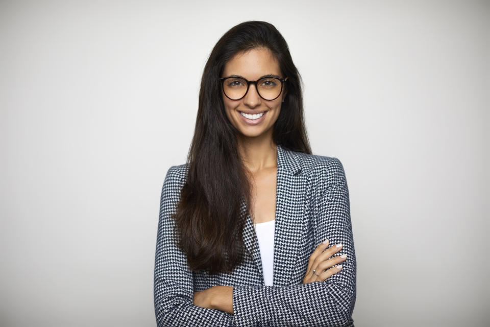Portrait of confident businesswoman against white background. Smiling female professional is standing with arms crossed. She is in formals.