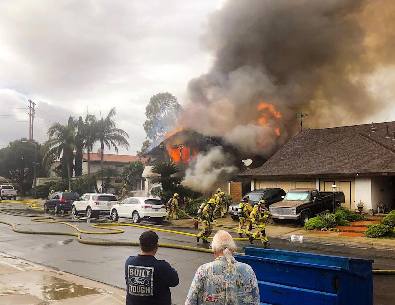 In this Sunday, Feb. 3, 2019 photo, provided by Kyle Vanderheide, Yorba Linda firefighters rush to a home engulfed in flames after a deadly small plane crash in Yorba Linda, Calif.