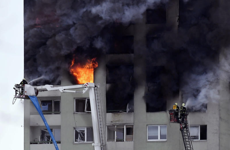 Firefighters on a ladder try to extinguish a fire in a 12-storey apartment block after a gas explosion in Presov, Slovakia, Friday, Dec. 6, 2019. Officials say a gas explosion in an apartment block in Slovakia has killed at least five people and others are trapped on the roof of the building. Firefighters say the explosion occurred in a 12-story building in the city of Presov shortly after noon on Friday.  (Frantisek Ivan/TASR via AP)