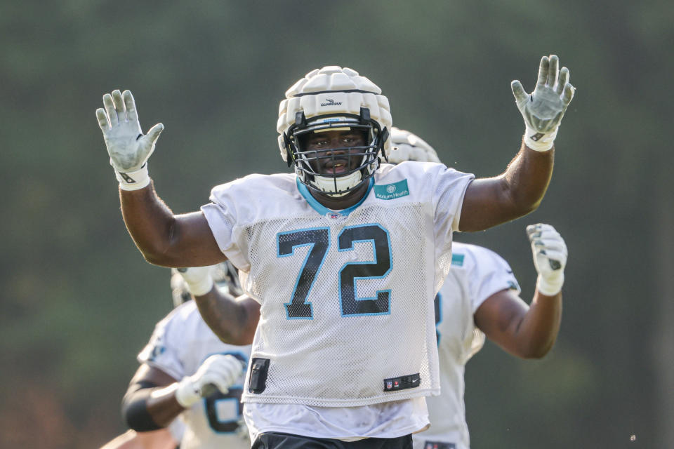 Carolina Panthers tackle Taylor Moton wears a Guardian Cap over his helmet to provide an extra layer of protection during practice at the NFL football team's training camp in Spartanburg, S.C., Tuesday, Aug. 10, 2021. (AP Photo/Nell Redmond)