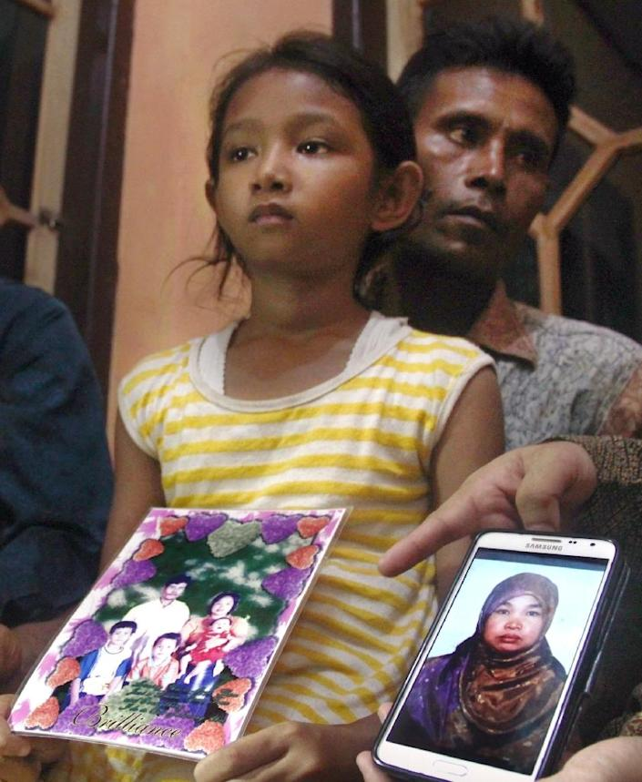 Desi Sri Rahayu, the ten-year-old daughter of Karni Binti Medi Tarsim, an Indonesian domestic worker executed in Saudi Arabia, holds a family potrait as she sits with her father Darpin at their home in Brebes in central Java on April 17, 2015 (AFP Photo/)