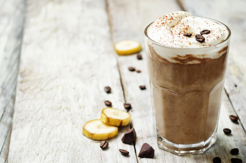 coffee chocolate banana smoothie with coconut whipped cream. toning. selective focus