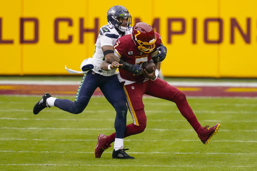 Washington Football Team quarterback Dwayne Haskins (7) is tackled by Seattle Seahawks strong safety Jamal Adams (33) during the first half of an NFL football game between the Seattle Seahawks and Washington Football Team, Sunday, Dec. 20, 2020, in Landover, Md. (AP Photo/Andrew Harnik)