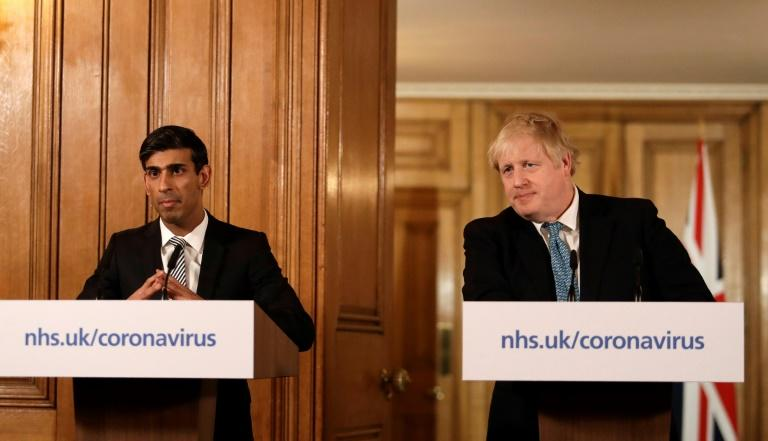 """Prime Minister Boris Johnson (R) said Britain needed to act """"like any wartime government,"""" as finance minister Rishi Sunak (L) unveiled a £330 billion ($400 billion, 363 billion euros) package of loans for virus-hit business"""