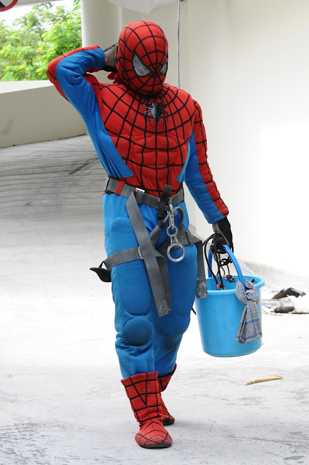 SURABAYA, INDONESIA - JULY 12: Indonesian 'Spider-Man' window cleaner, 37-year-old Teguh is seen after cleaning the glass windows of the 18-storey Alana Hotel on July 12, 2013 in Surabaya, Indonesia. Teguh is a specialist glass window cleaner working on high-rise buildings wearing a Spider-Man uniform and working at an altitude of over 500 meters above ground level. He earns between Rp. 5 million and 15 million depending on the height of the building and the level of difficulty. (Photo by Robertus Pudyanto/Getty Images)