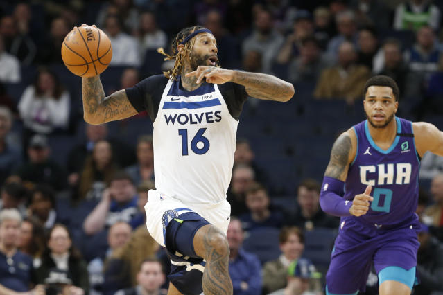 Minnesota Timberwolves' James Johnson, left, looks to pass the ball as Charlotte Hornets' Miles Bridges pursues during the first half of an NBA basketball game Wednesday, Feb. 12, 2020, in Minneapolis. (AP Photo/Jim Mone)