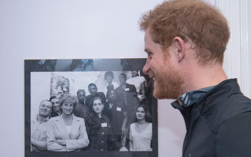 Prince Harry with a picture of his mother Princess Diana, with staff and users of The Running Charity, which is the UK's first running-orientated programme for homeless and vulnerable young people, in Willesden in north west London. - Credit: Geoff Pugh