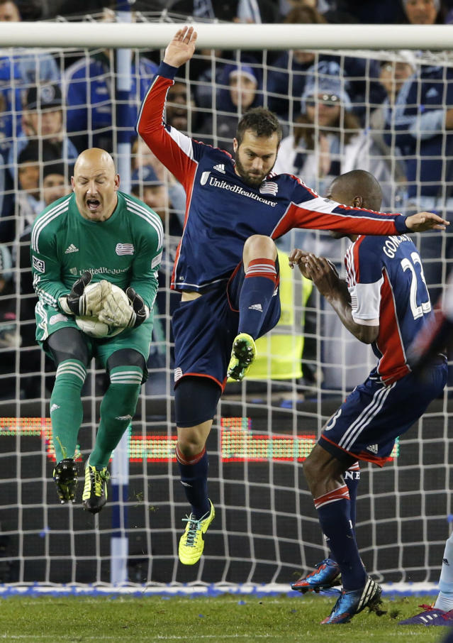 New England Revolution goalkeeper Matt Reis, left, makes a save next to New England Revolution defenders A.J. Soares, middle, and Jose Goncalves (23) during the second half of an MLS playoff soccer match against Sporting Kansas City in Kansas City, Kan., Wednesday, Nov. 6, 2013. (AP Photo/Orlin Wagner)