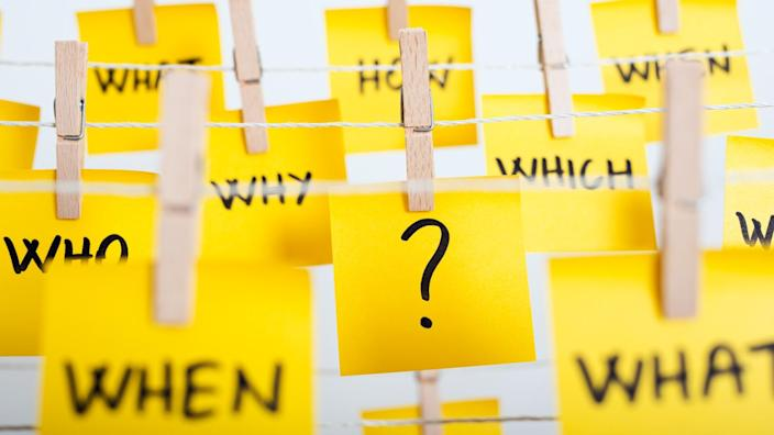 adhesive note papers with question mark and w questions hanging on the rope.
