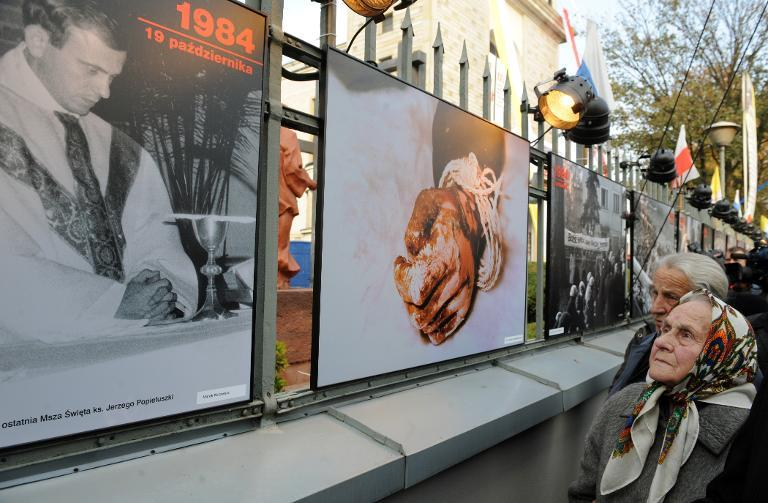 Marianna Popieluszko, mother of late Catholic priest Jerzy Popieluszko looking at a pictures in Warsaw of her son. The photo on the right shows his hand after his bound remains were found in a waterway in 1984