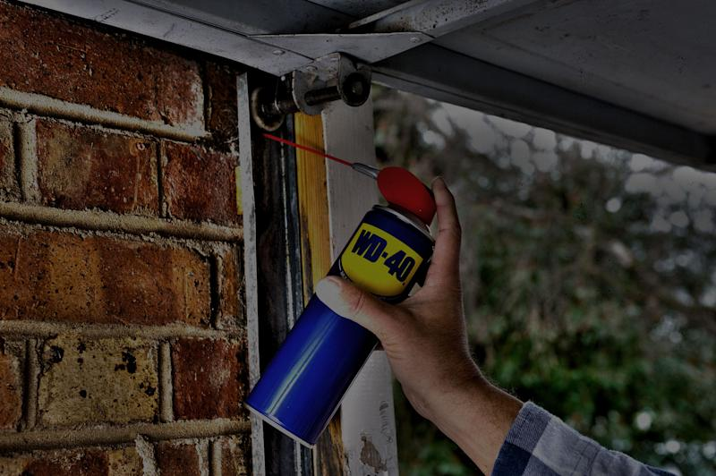 A man's hand using a can of WD-40 in a garage.