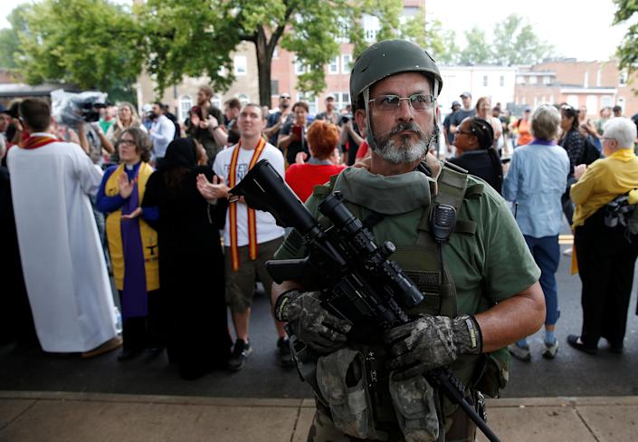 <p>A white supremacist militia member stands in front of clergy counter protesting during rally in Charlottesville, Va., Aug. 12, 2017. (Photo: Joshua Roberts/Reuters) </p>