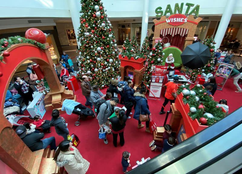 FILE PHOTO: Families wait in line to meet Santa Claus at Fashion Centre at Pentagon City, decorated for the holidays, in Arlington, Virginia