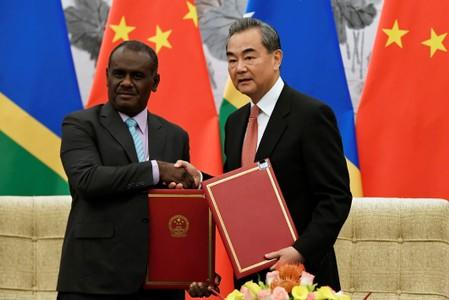 Chinese State Councilor and Foreign Minister Wang Yi shakes hands with Solomon Islands Foreign Minister Jeremiah Manele during a ceremony in Beijing