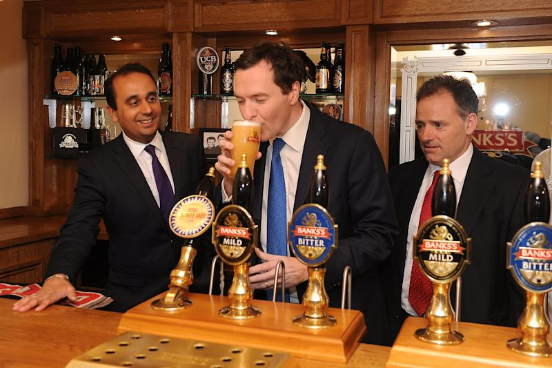 Chancellor George Osborne with a pint of Sunbeam ale alongside Conservative MP for Wolverhampton south west Paul Uppal (left) and chief executive Ralph Findlay (right) during a visit to Marston's Brewery in Wolverhampton.