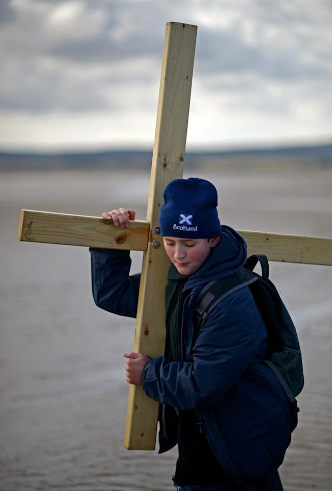 BERWICK-UPON-TWEED, ENGLAND - MARCH 29:  Pilgrims walk with crosses as the Northern Cross pilgrimage undertakes its final leg of the journey to Holy Island on March 29, 2013 in Berwick-upon-Tweed, England. More than 50 people, young and old, celebrated Easter by crossing the tidal causeway during the annual Christian pilgrimage. Every year people of all ages, from all over the world and from all realms of Christian life walk together at Easter to Holy Island.  (Photo by Jeff J Mitchell/Getty Images)