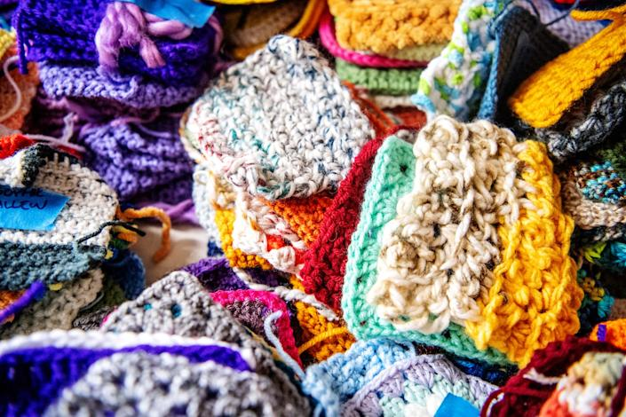 A photo of a colorful pile of hand-knitted squares sent to TikTok sensation Liv Huffman