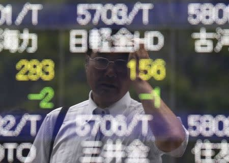 A man wipes his head as he is reflected on a stock quotation board outside a brokerage in Tokyo June 10, 2014. REUTERS/Issei Kato