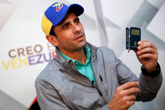 Venezuelan opposition leader and Governor of Miranda state Henrique Capriles holds a copy of the Venezuelan constitution as he speaks during an interview with Reuters in Caracas, Venezuela May 26, 2016. REUTERS/Carlos Garcia Rawlins