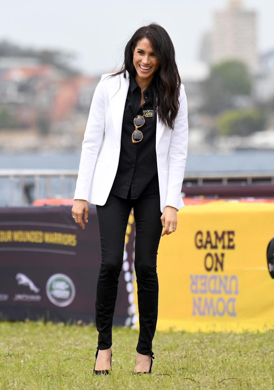 <p>For an Invictus Games event on day six of the couple's Australian royal tour, Meghan teamed a white Altuzarra blazer with an Invictus Sydney shirt. She finished the look with £159 Mother Demin jeans, $240 (approx £184) Illesteva sunglasses and her go-to £566 Tabitha Simmons pumps. <em>[Photo: Getty]</em> </p>