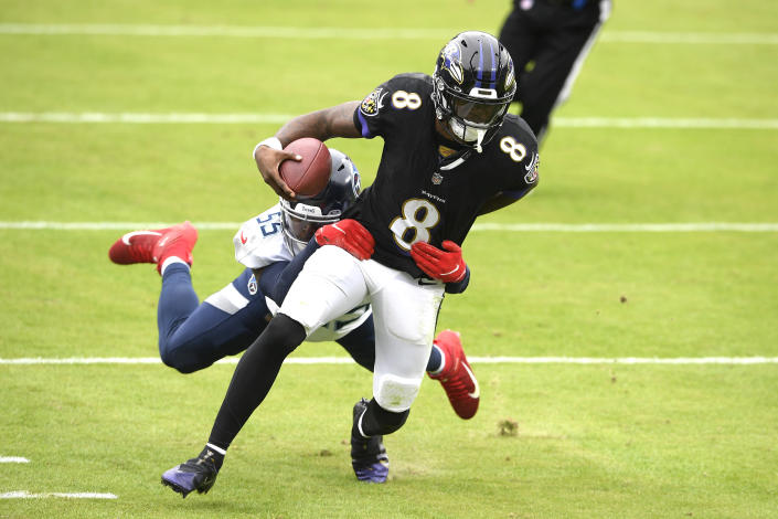 Baltimore Ravens quarterback Lamar Jackson (8) runs with the ball while Tennessee Titans inside linebacker Jayon Brown tries to stop him during the first half of an NFL football game, Sunday, Nov. 22, 2020, in Baltimore. (AP Photo/Nick Wass)