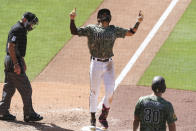 San Diego Padres' Fernando Tatis Jr., center, points skyward as he crosses home plate after hitting a grand slam off Seattle Mariners relief pitcher Robert Dugger in the seventh inning of a baseball game Sunday, May 23, 2021, in San Diego. (AP Photo/Derrick Tuskan)