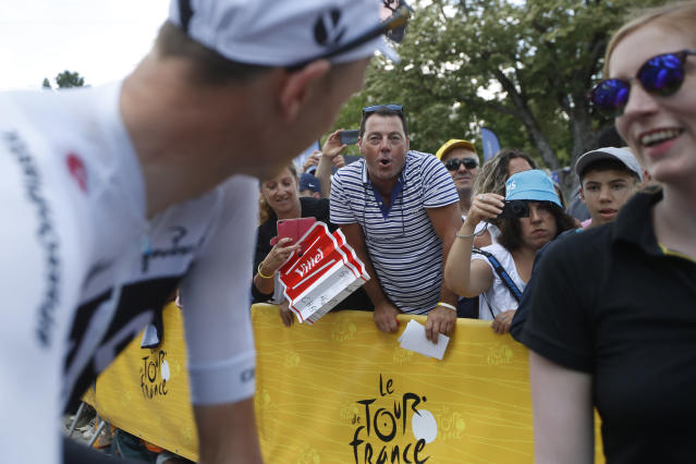 A man, center, expresses his disapproval of Britain's Chris Froome, left, by booing prior to the start of the fifteenth stage of the Tour de France cycling race over 181.5 kilometers (112.8 miles) with start in Millau and finish in Carcassonne, France, France, Sunday July 22, 2018. Froome was cleared of doping by the International Cycling Union in a decision that will allow him to pursue a record-tying fifth Tour de France (AP Photo/Christophe Ena )
