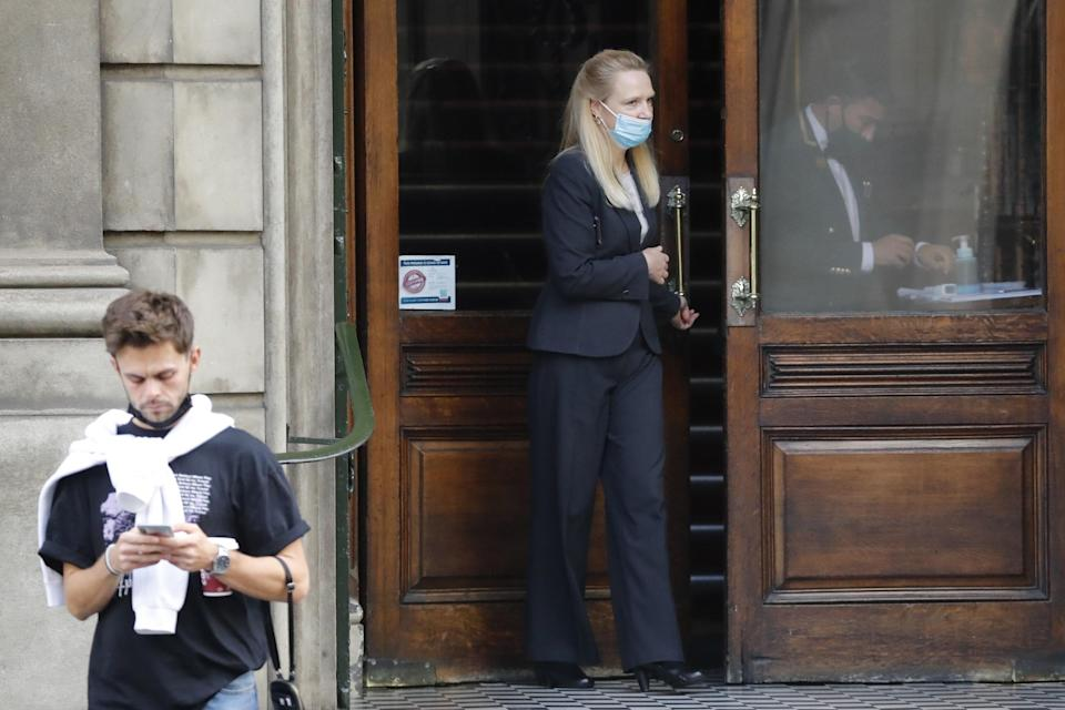An employee (R) is pictured through the glass door as another employee stands on the steps of the private members' Garrick Club