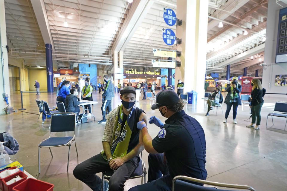 FILE - In this May 2, 2021, file photo, Austin Kennedy, left, a Seattle Sounders season ticket holder, gets the Johnson & Johnson COVID-19 vaccine at a clinic in a concourse at Lumen Field prior to an MLS soccer match between the Sounders and the Los Angeles Galaxy. Air travel in the U.S. hit its highest mark since COVID-19 took hold more than 13 months ago, while European Union officials are proposing to ease restrictions on visitors to the continent as the vaccine rollout sends new cases and deaths tumbling in more affluent countries. (AP Photo/Ted S. Warren, File)