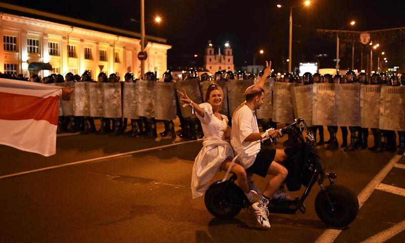 Protesters on a scooter face off with riot police after polls closed in Minsk