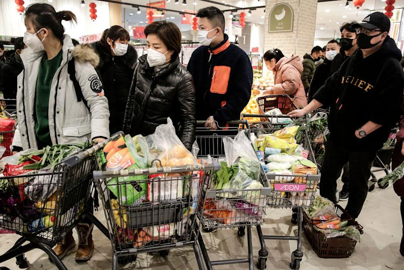 Pictured are several shoppers wearing masks with trolleys full of food at a Wuhan supermarket.