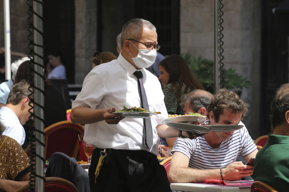 A restaurant employee serves meals in a restaurant of Saint Jean de Luz, southwestern France, Tuesday June 2, 2020. The French way of life resumes Tuesday with most virus-related restrictions easing as the country prepares for the summer holiday season amid the pandemic. Restaurants and cafes reopen Tuesday with a notable exception for the Paris region, the country's worst-affected by the virus, where many facilities will have to wait until June 22 to reopen. (AP Photo/Bob Edme)