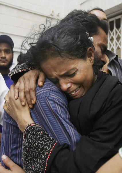 Family members mourn the death of a man outside a mortuary in Karachi, Pakistan, Wednesday, Sept. 12, 2012. Pakistani officials say the death toll from devastating factory fires that broke out in two major cities has killed dozens. (AP Photo/Fareed Khan)
