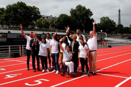 Paris Mayor Anne Hidalgo (3rlL) and former Olympic champion Guy Drut (R) pose with French athletes and members of the CNOSF on an athletics track installed on the River Seine in Paris, France, June 23, 2017 as Paris transforms into a giant Olympic park to celebrate International Olympic Days with a variety of sporting events for the public across the city during two days as the city bids to host the 2024 Olympic and Paralympic Games. At 2ndL President of the French National Olympic and Sports Committee (CNOSF) Denis Masseglia, Tony Estanguet (5thL), co-president of the Paris candicacy for the 2024 Olympics, French Sports minister Laura Flessel (C), Ile de France region President Valerie Pecresse (4thR), and President of the French Paralympic Committee Emmanuelle Assman  (C front).  REUTERS/Jean-Paul Pelissier