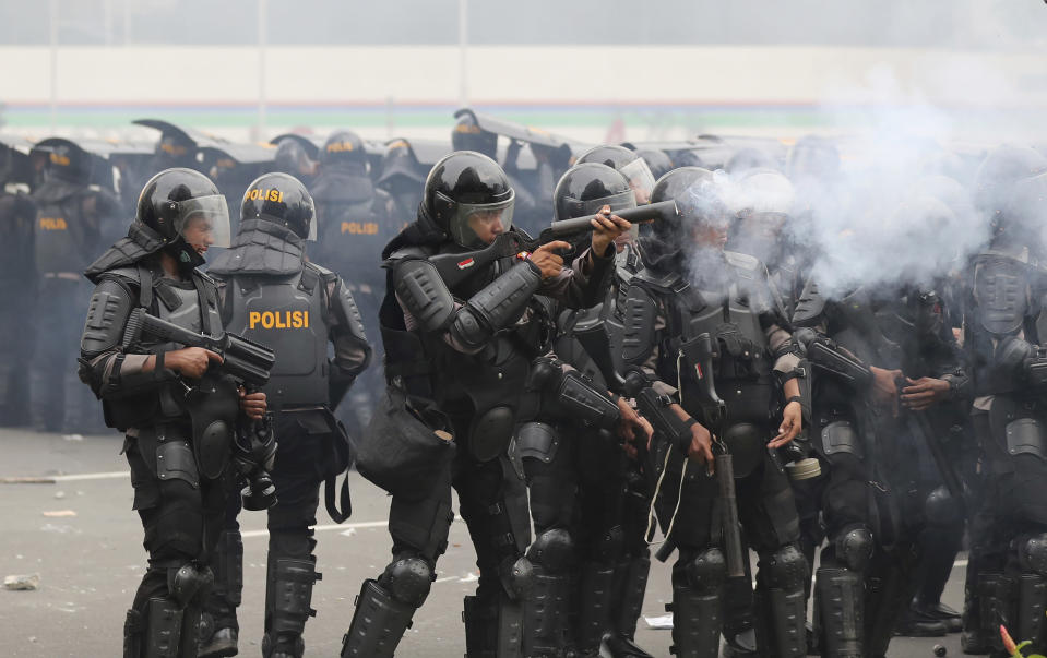 A police officer fires a projectile during a rally against a controversial bill on job creation in Jakarta, Indonesia, Thursday, Oct. 8, 2020. Thousands of enraged students and workers staged rallies across Indonesia on Thursday in opposition to the new law they say will cripple labor rights and harm the environment. (AP Photo/Tatan Syuflana)