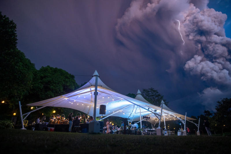 Chino Vaflor and Kat Bautista Palomar who marry in Alfonso, Cavite in the Philippines a short distance from the Taal volcano. Lightning and smoke is seen in the sky.