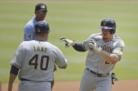 Milwaukee Brewers' Willy Adames, right, celebrates with third base coach Jason Lane (40) after hitting a home run off Atlanta Braves' Charlie Morton during the first inning of a baseball game Sunday, Aug. 1, 2021, in Atlanta. (AP Photo/Ben Margot)