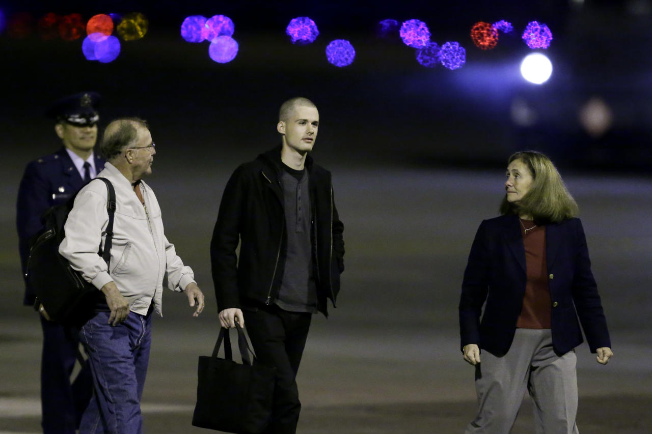 Matthew Miller, center, who had been held in North Korea since April, 2014, is greeted after arriving Saturday, Nov. 8, 2014, at Joint Base Lewis-McChord, Wash., after he were freed during a top-secret mission. (AP Photo/Ted S. Warren)