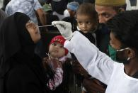 A health worker collects a swab sample for COVID-19 test at a train station in Mumbai, India, Thursday, July 22, 2021. (AP Photo/Rajanish Kakade)